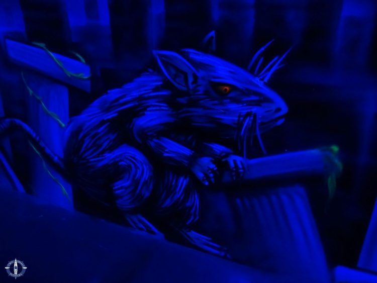 Giant creepy rat in black light on the wall at Laser District, Switzerland