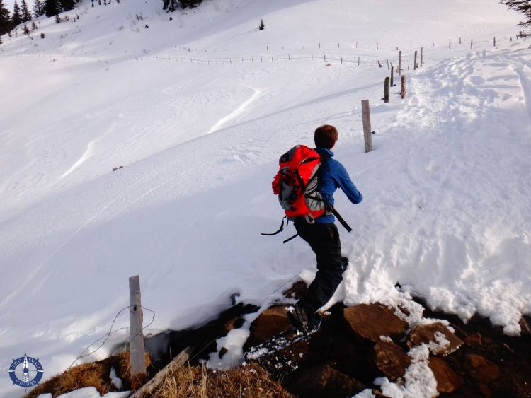 Travis hops across an alpine creek while snowshoeing in Switzerland's La Berra ski area