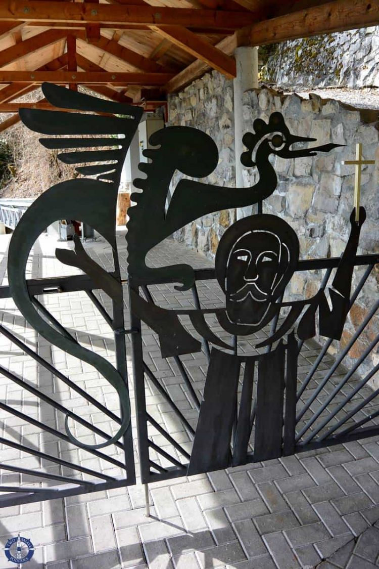 Gate at St Beatus Caves showing the saint defeating the dragon