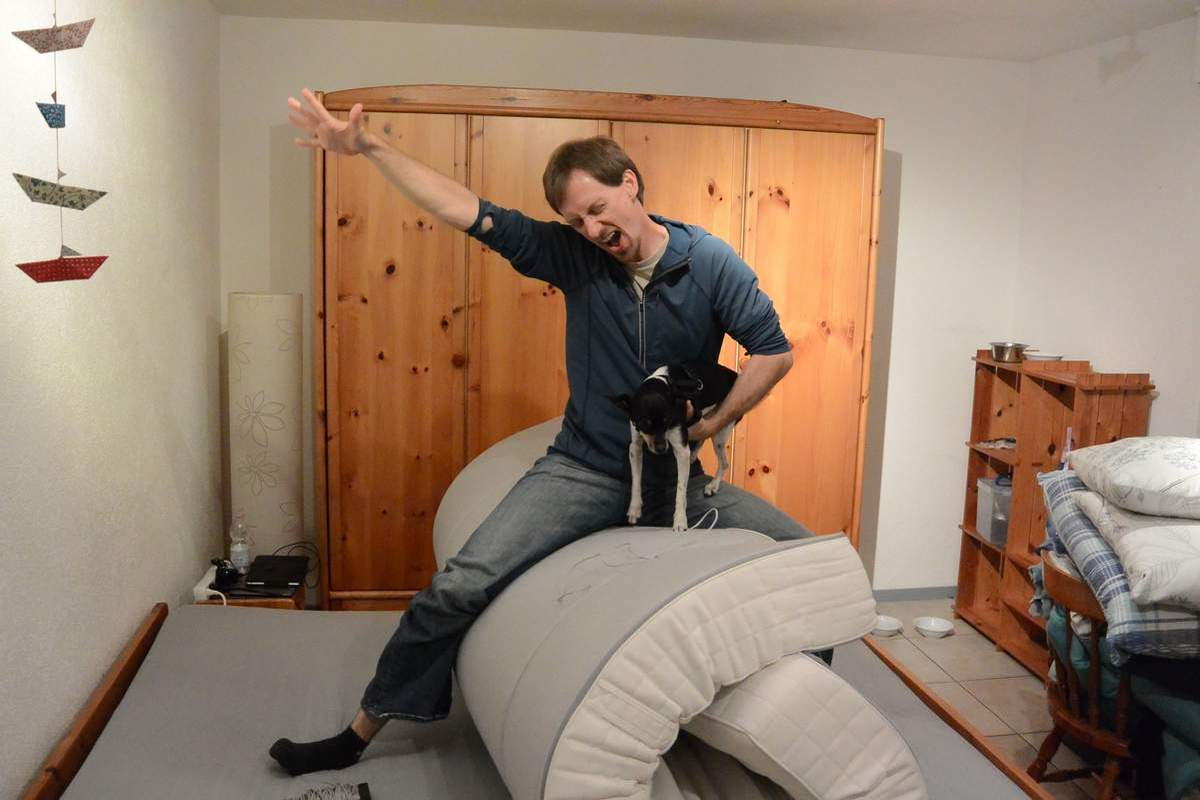 Travis rides our rolled up mattress like a bronc