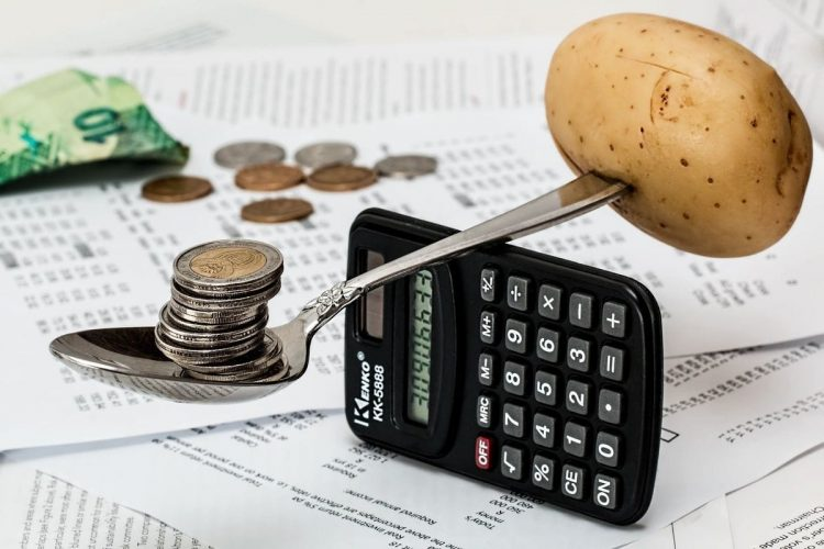 Money being weighed on a spoon against a potato