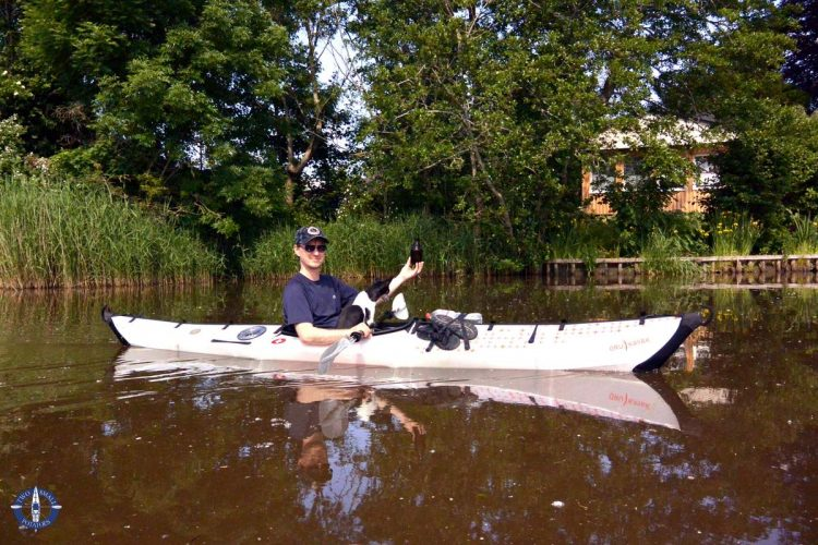 Travis collects garbage while paddling the Medem River in Germany